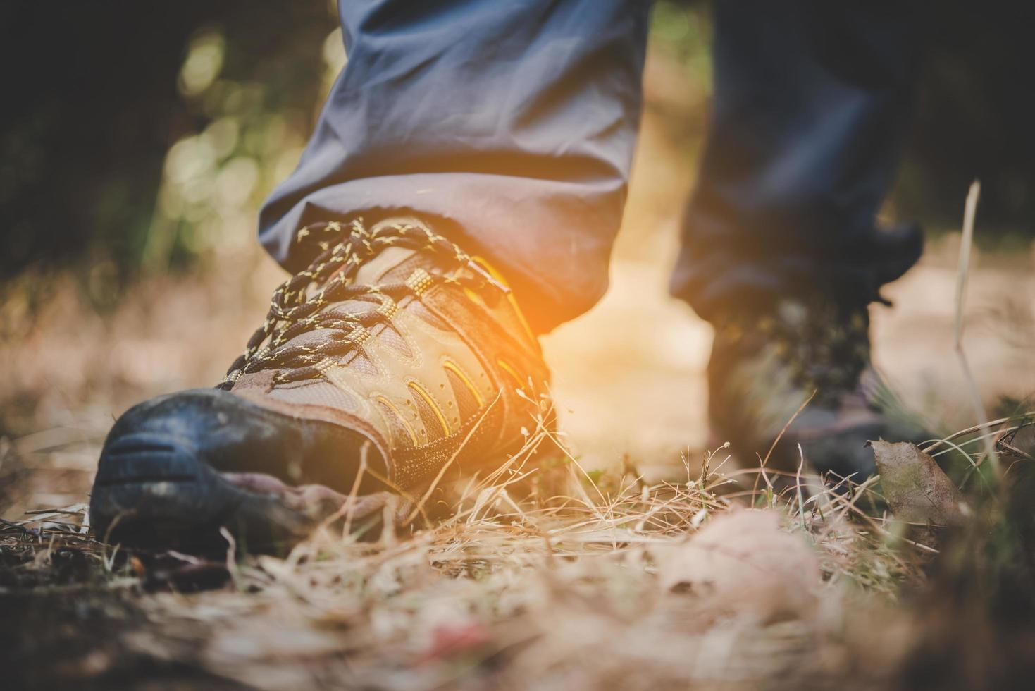 Nahaufnahme der Füße eines Mannes, die auf einem Bergweg wandern foto