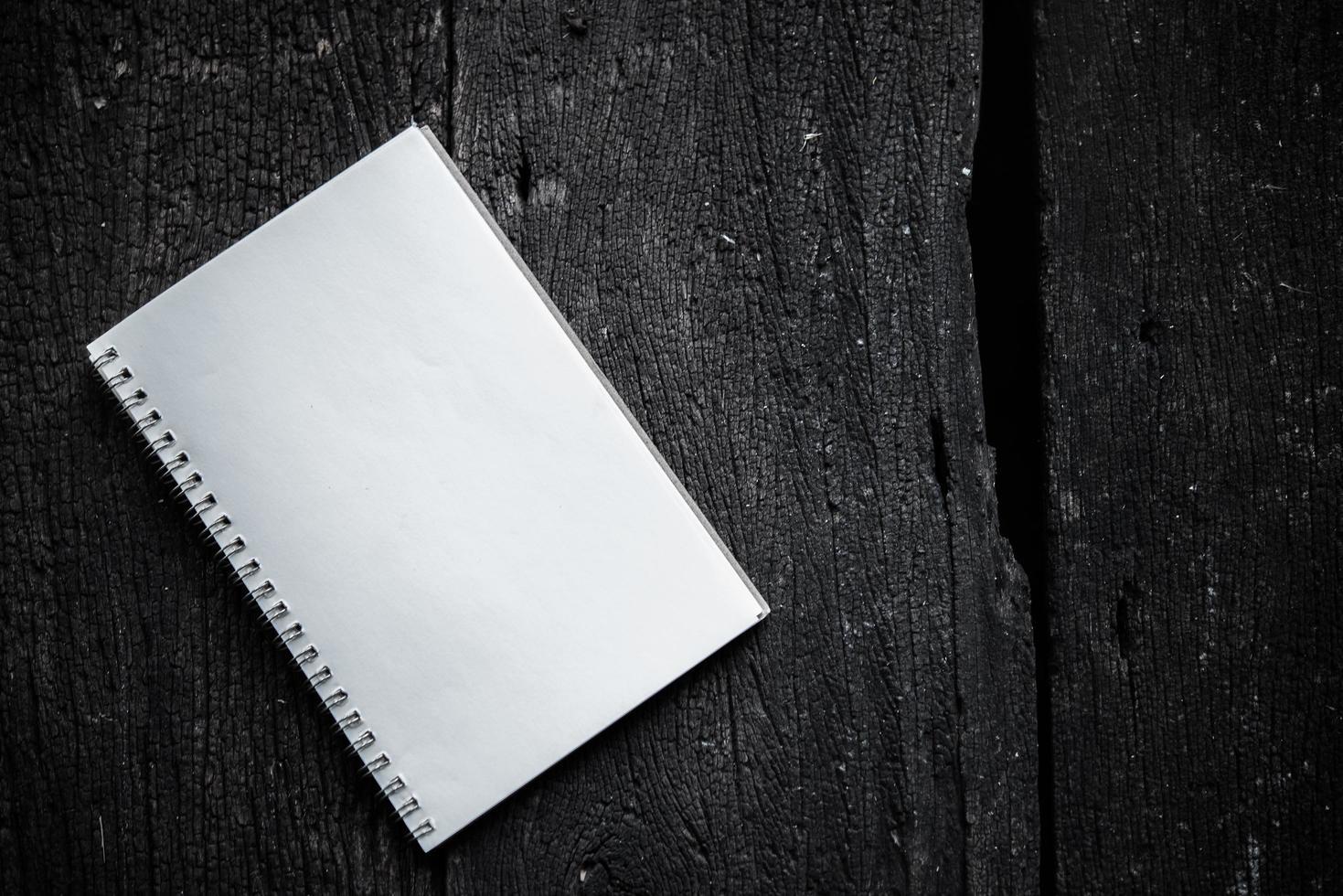 Notizbuch auf Holzbeschaffenheitshintergrund foto