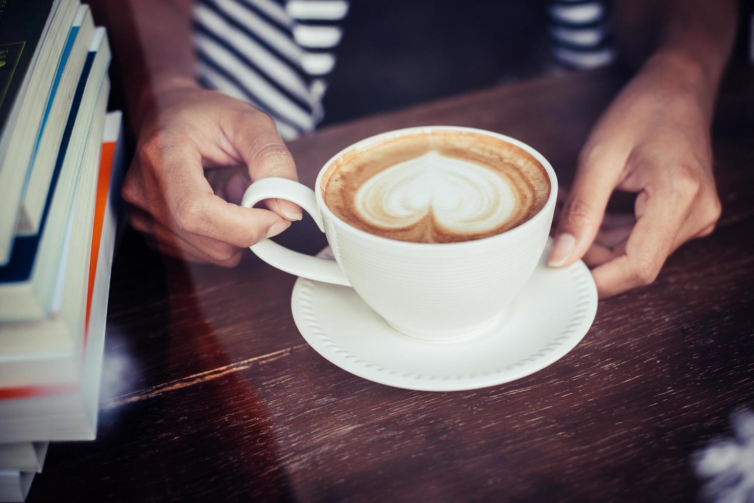 Frauenhände, die mit Kaffee im Café entspannen foto