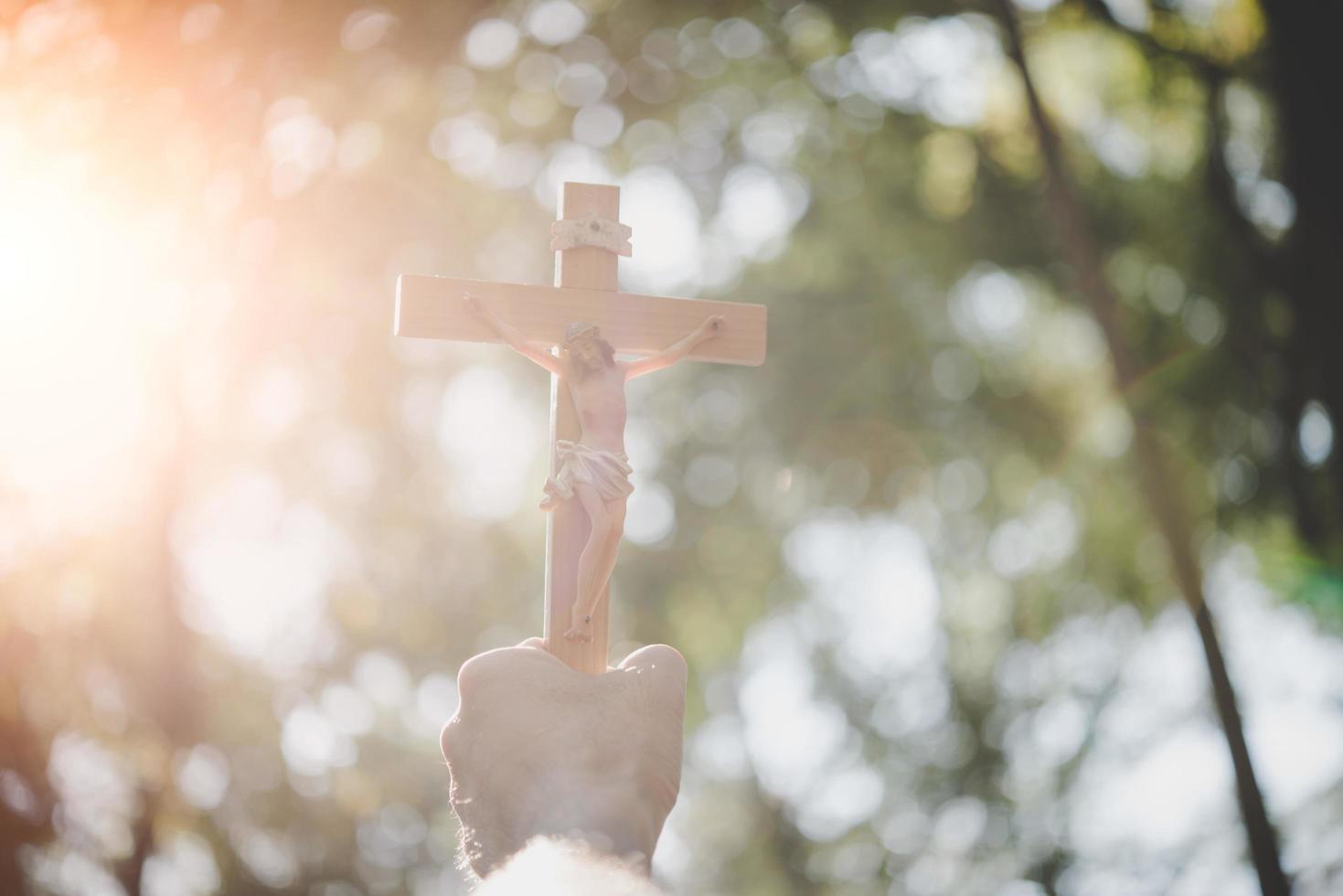 Hände halten ein Holzkreuz über dem Himmel foto