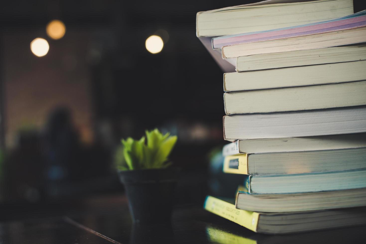 Stapel von Büchern auf einem Tisch über einem unscharfen Bibliothekshintergrund foto