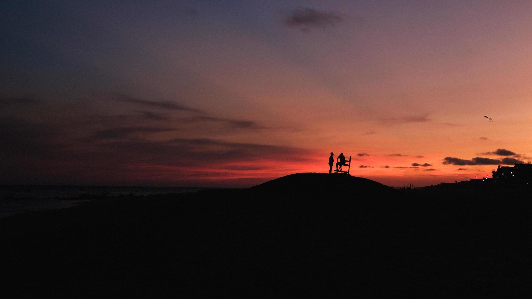 Schattenbild von 2 Personen, die auf Hügel während Sonnenuntergang stehen foto