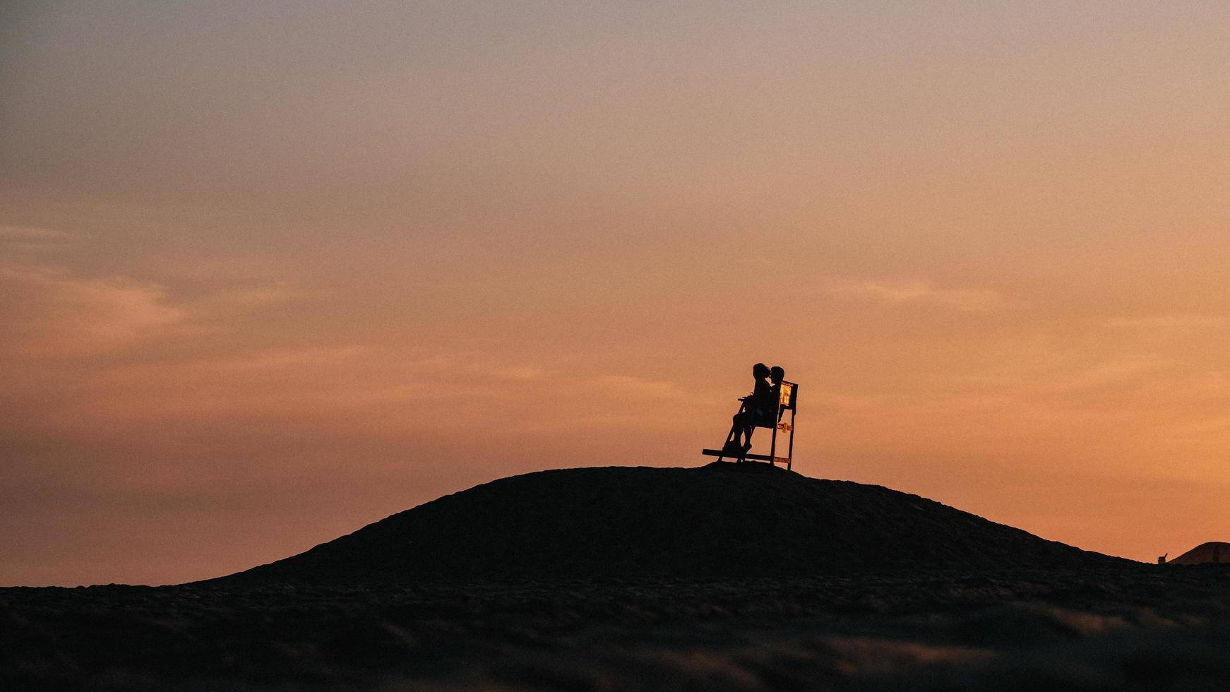 Schattenbild von 2 Personen, die oben auf Berg während Sonnenuntergang stehen foto