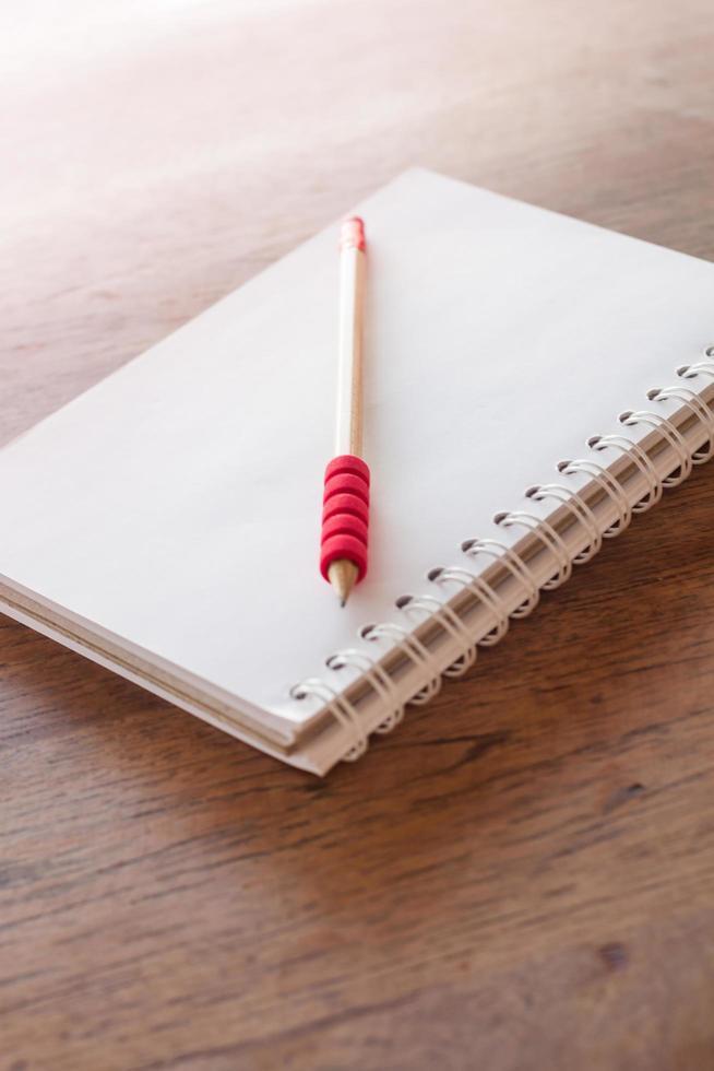Rotstift und ein Notizbuch im Sonnenlicht foto