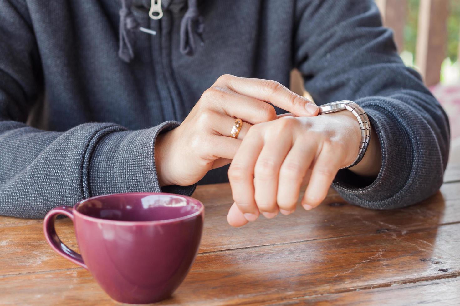 Person, die die Uhrzeit auf ihrer Uhr überprüft foto