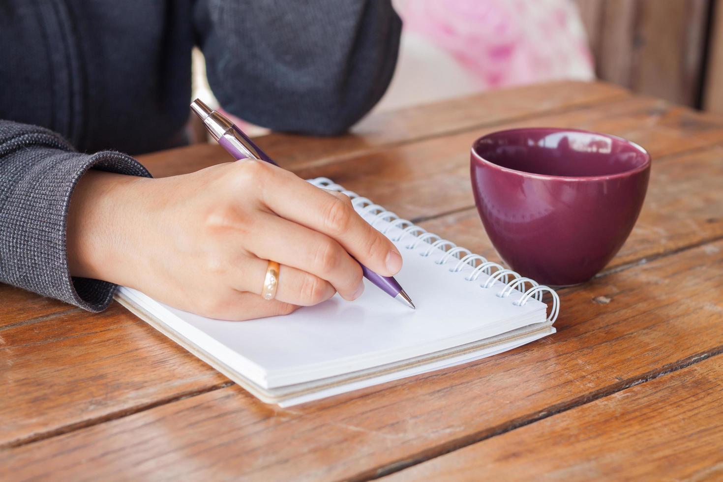 Person, die in ein Notizbuch mit einem Kaffee schreibt foto