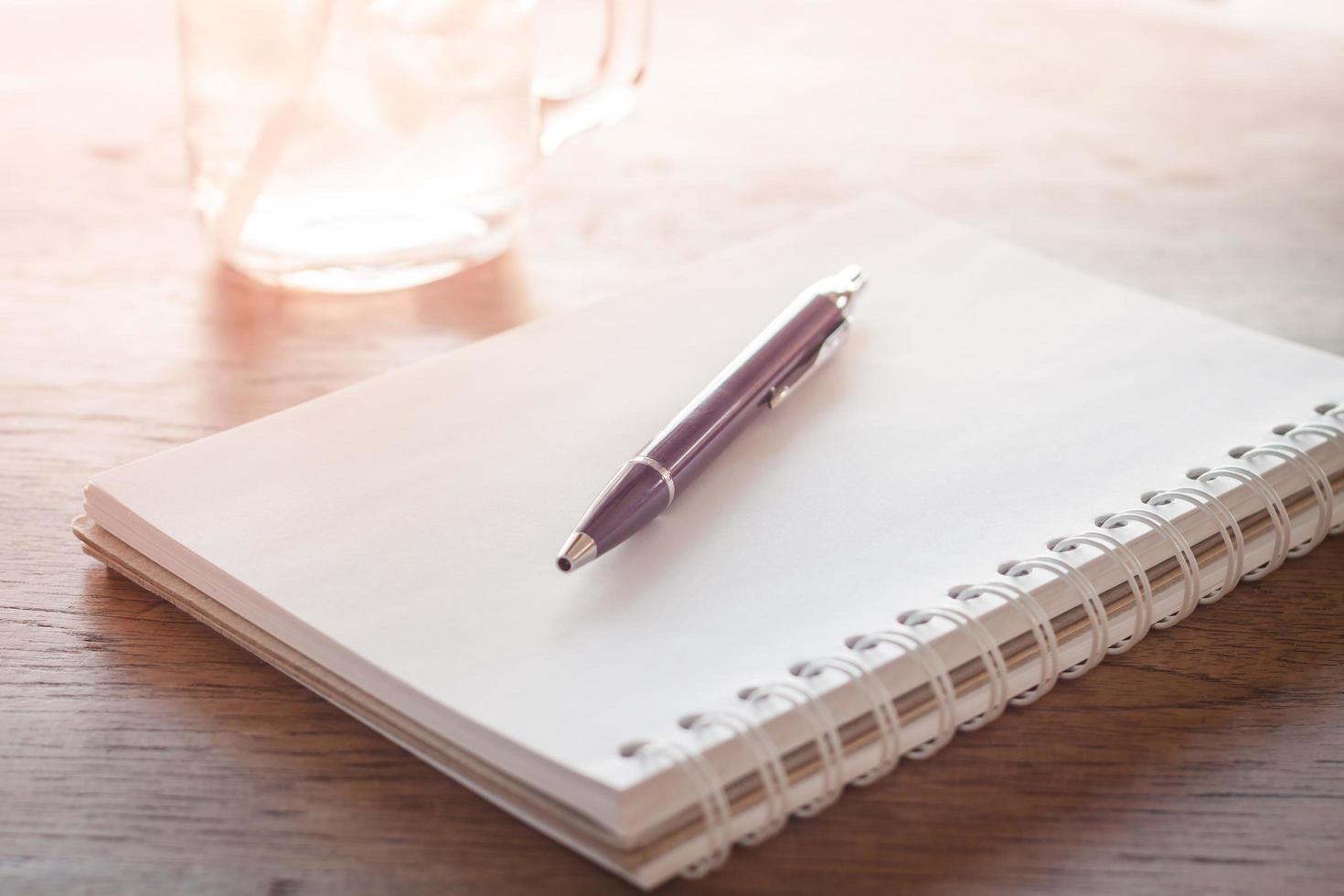 Sonnenlicht auf einem Notizbuch und Stift foto