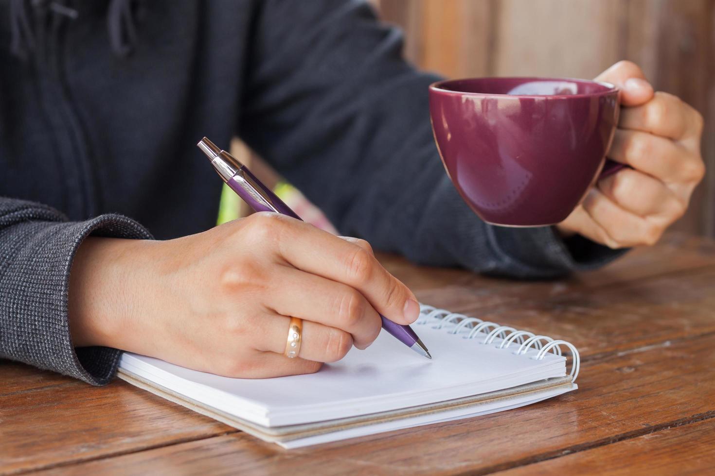 Person, die Notizen macht und einen Kaffee hält foto