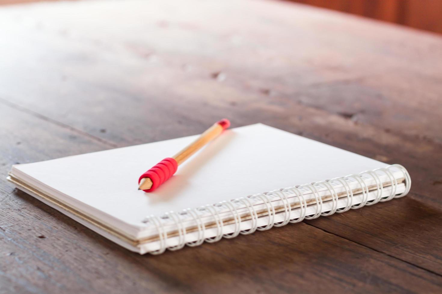 Rotstift auf einem Notizbuch auf einem Tisch foto