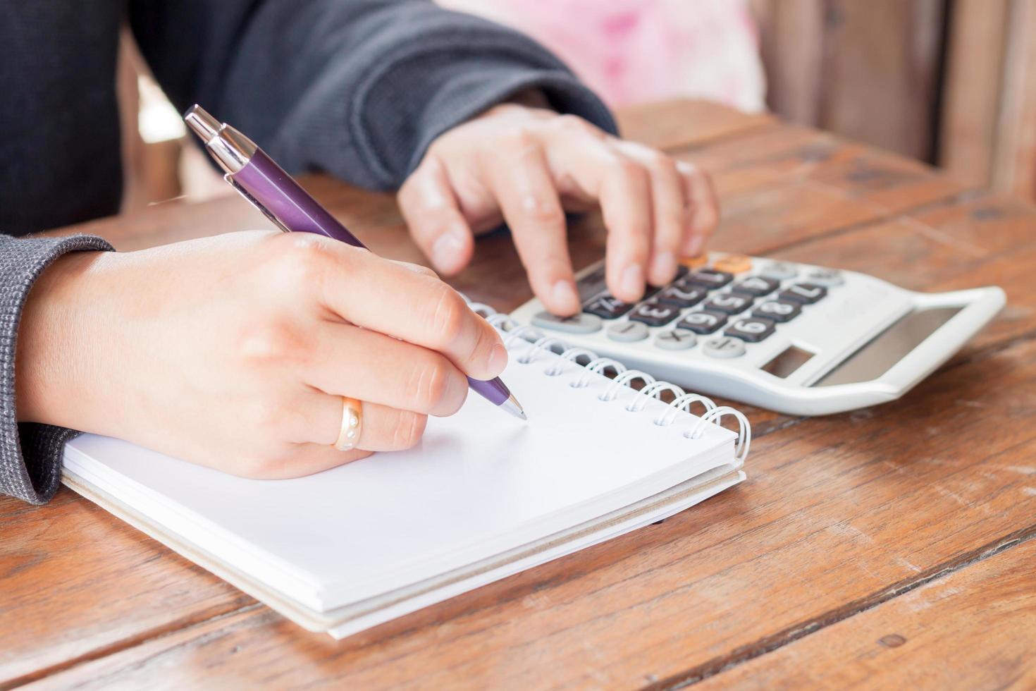 Person, die Notizen schreibt und Berechnungen vornimmt foto