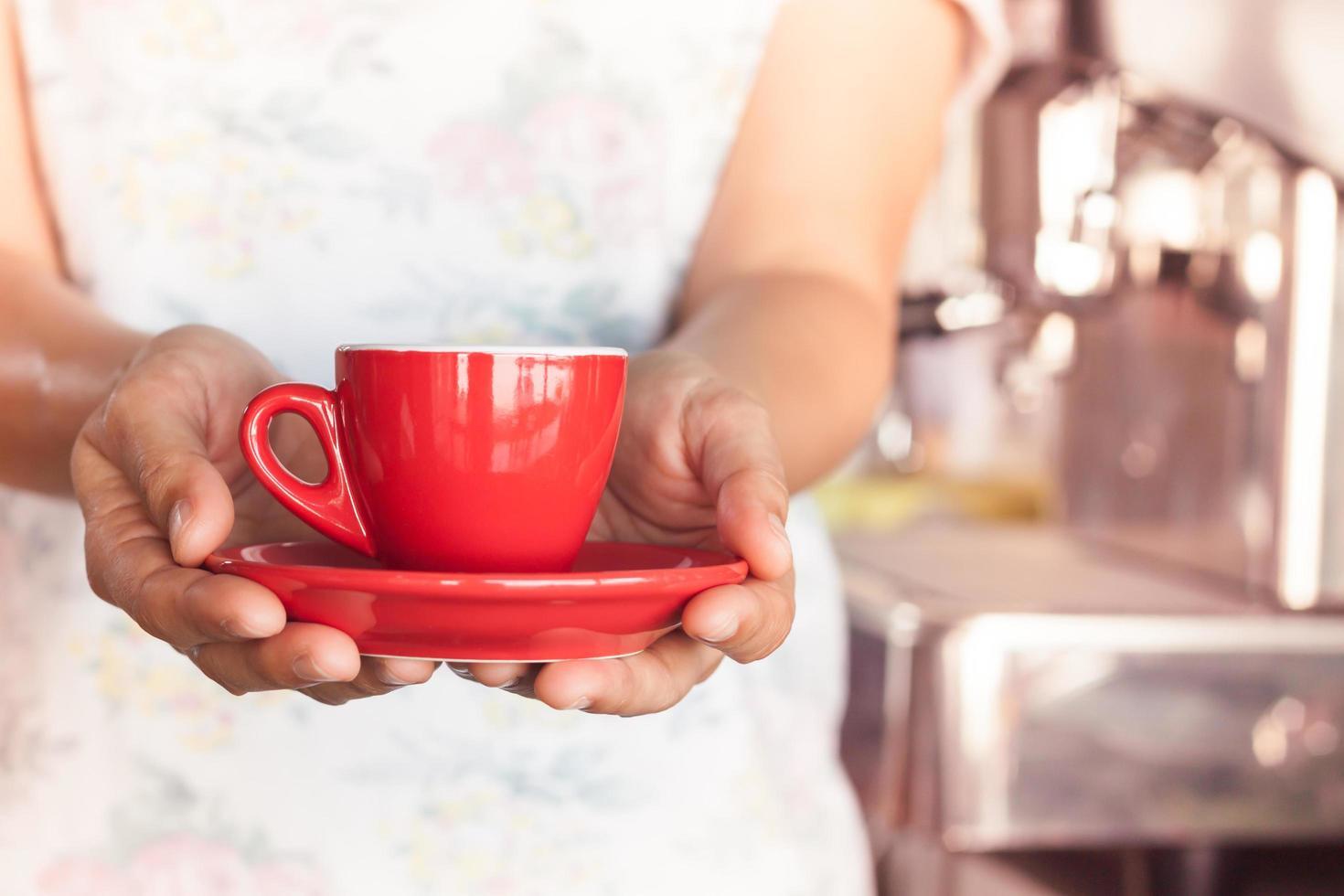 Frau hält eine rote Kaffeetasse foto