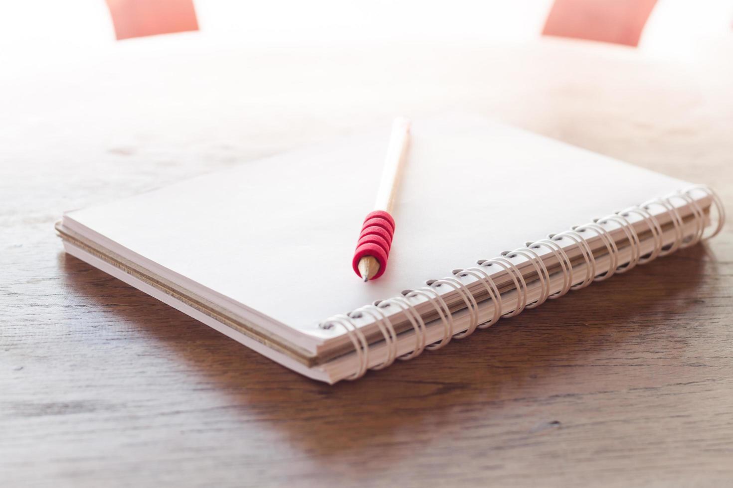 Notizbuch und ein roter Stift im Sonnenlicht foto