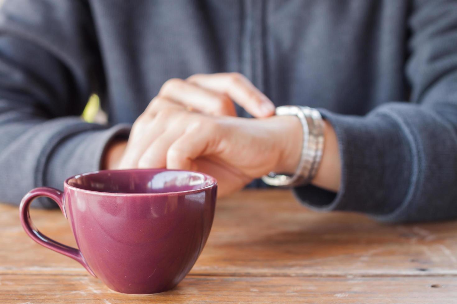 Person, die die Zeit mit einer Kaffeetasse überprüft foto