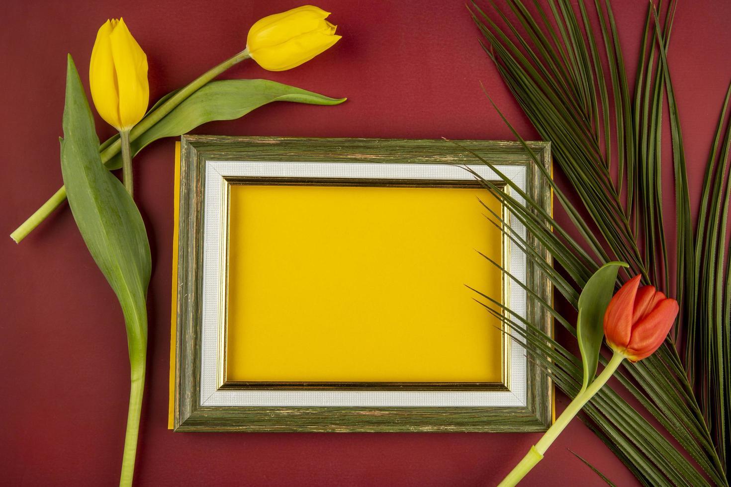 Draufsicht auf einen leeren Bilderrahmen mit Tulpen und einem Palmblatt foto
