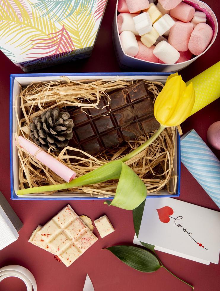 Draufsicht einer Schachtel mit Blumen, Schokolade und Süßigkeiten foto