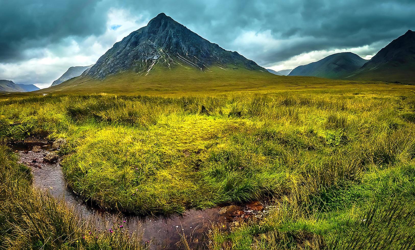 Berge und eine Wiese unter einem bewölkten Himmel foto