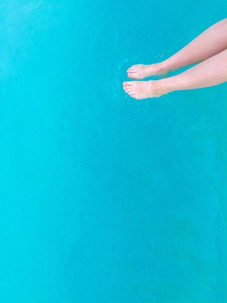 Person, die Füße in einen Pool taucht foto