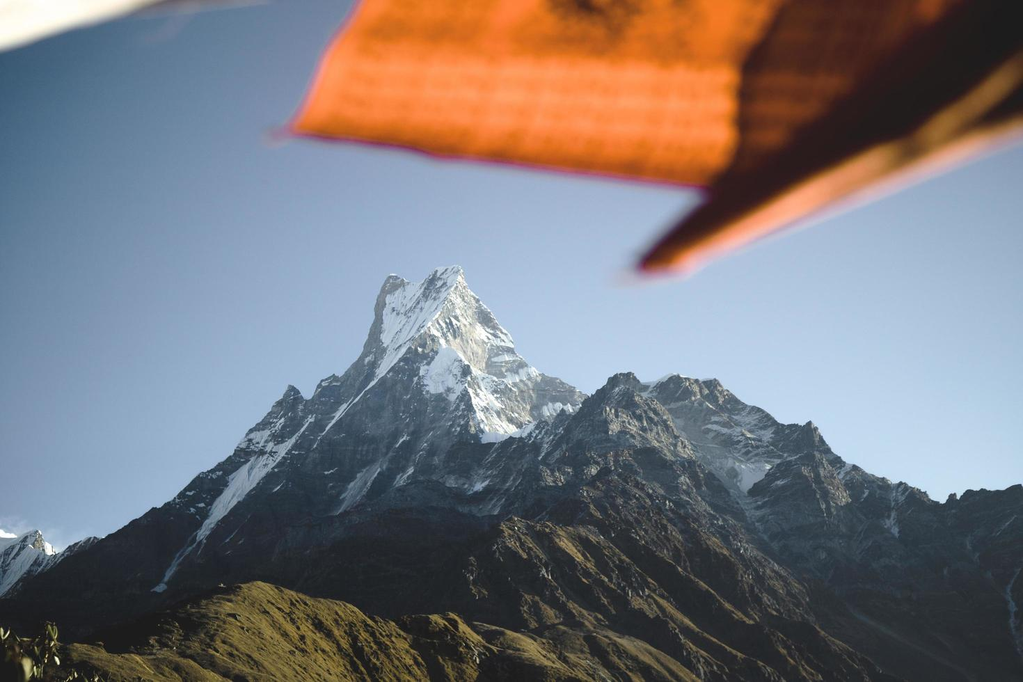 orange und weiße Flagge oben auf einem Berg foto