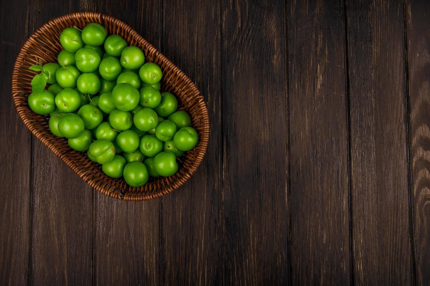 Draufsicht der grünen sauren Pflaumen in einem Weidenkorb auf dunklem hölzernem Hintergrund foto