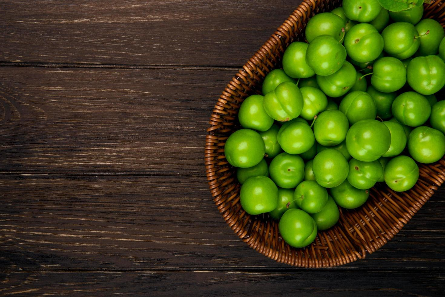Draufsicht der grünen Pflaumen in einem Weidenkorb auf dunklem hölzernem Hintergrund mit Kopienraum foto