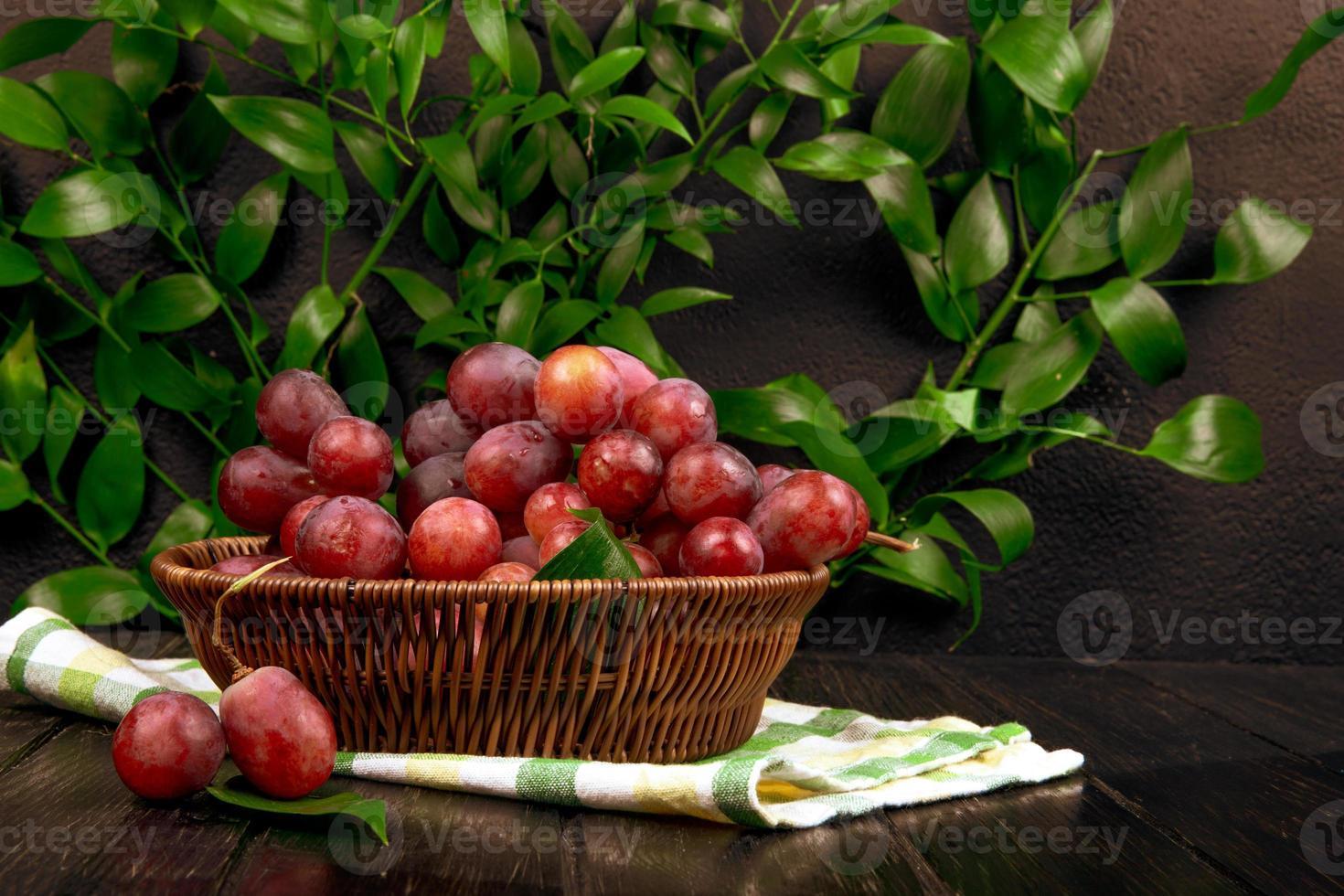 rote Trauben in einem Weidenkorb auf Holzoberfläche foto