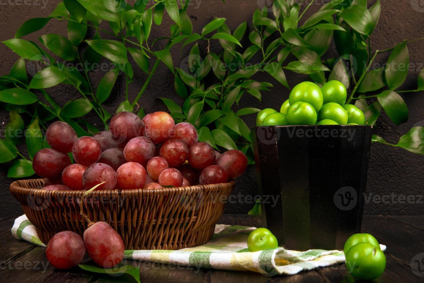 rote Trauben und saure Pflaumen in Schalen foto