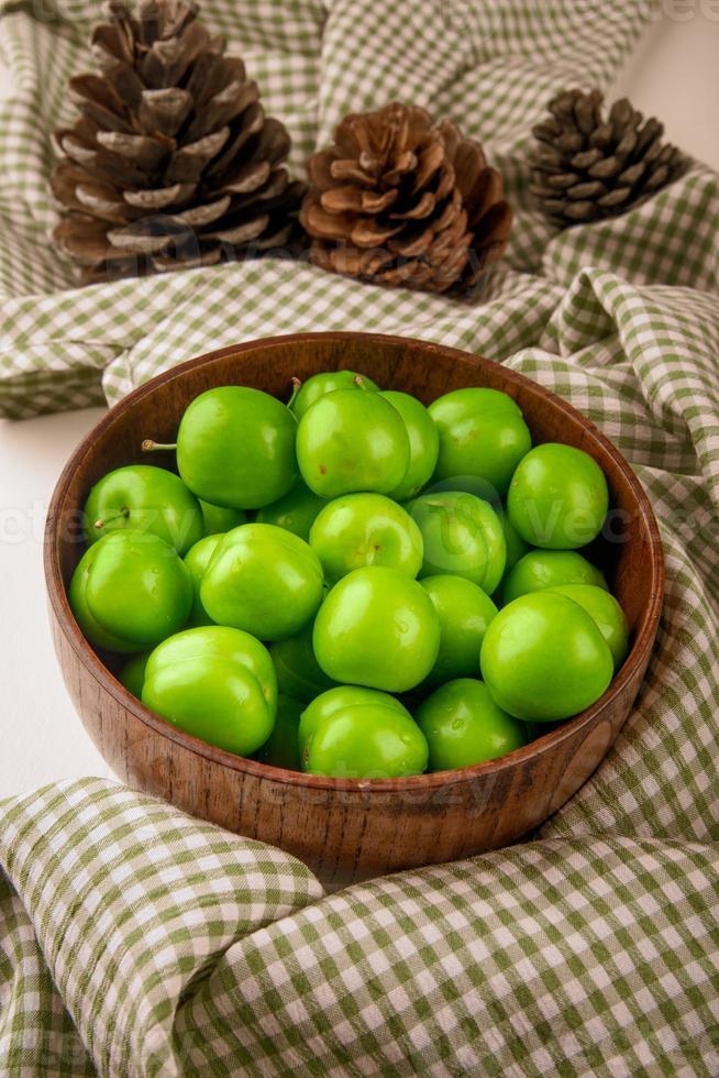 Schüssel mit grünen sauren Pflaumen foto