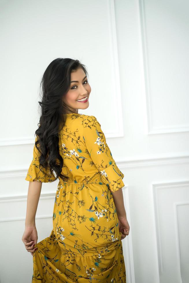 junge Frau, die ein gelbes Kleid trägt, das Kamera betrachtet foto
