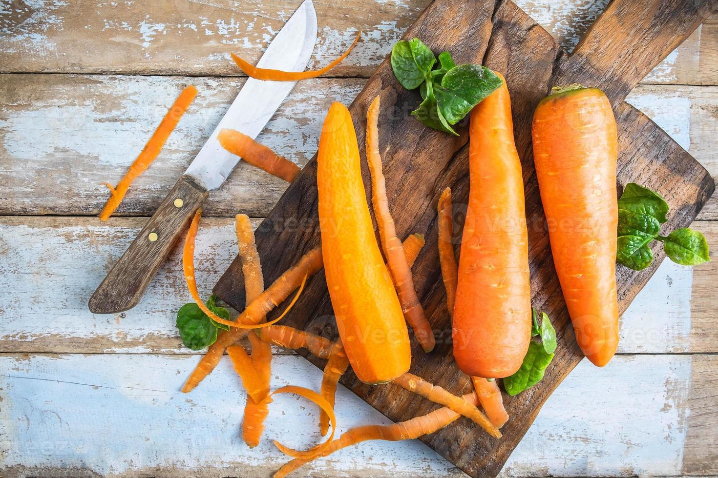 Karotten mit einem Messer auf einem Schneidebrett foto