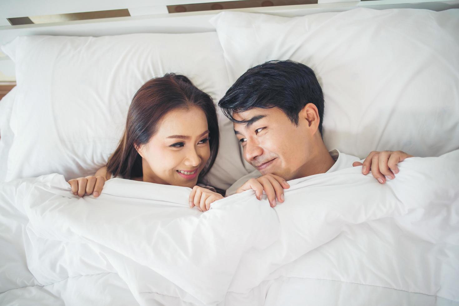 glückliches Paar, das zusammen in ihrem Bett liegt foto