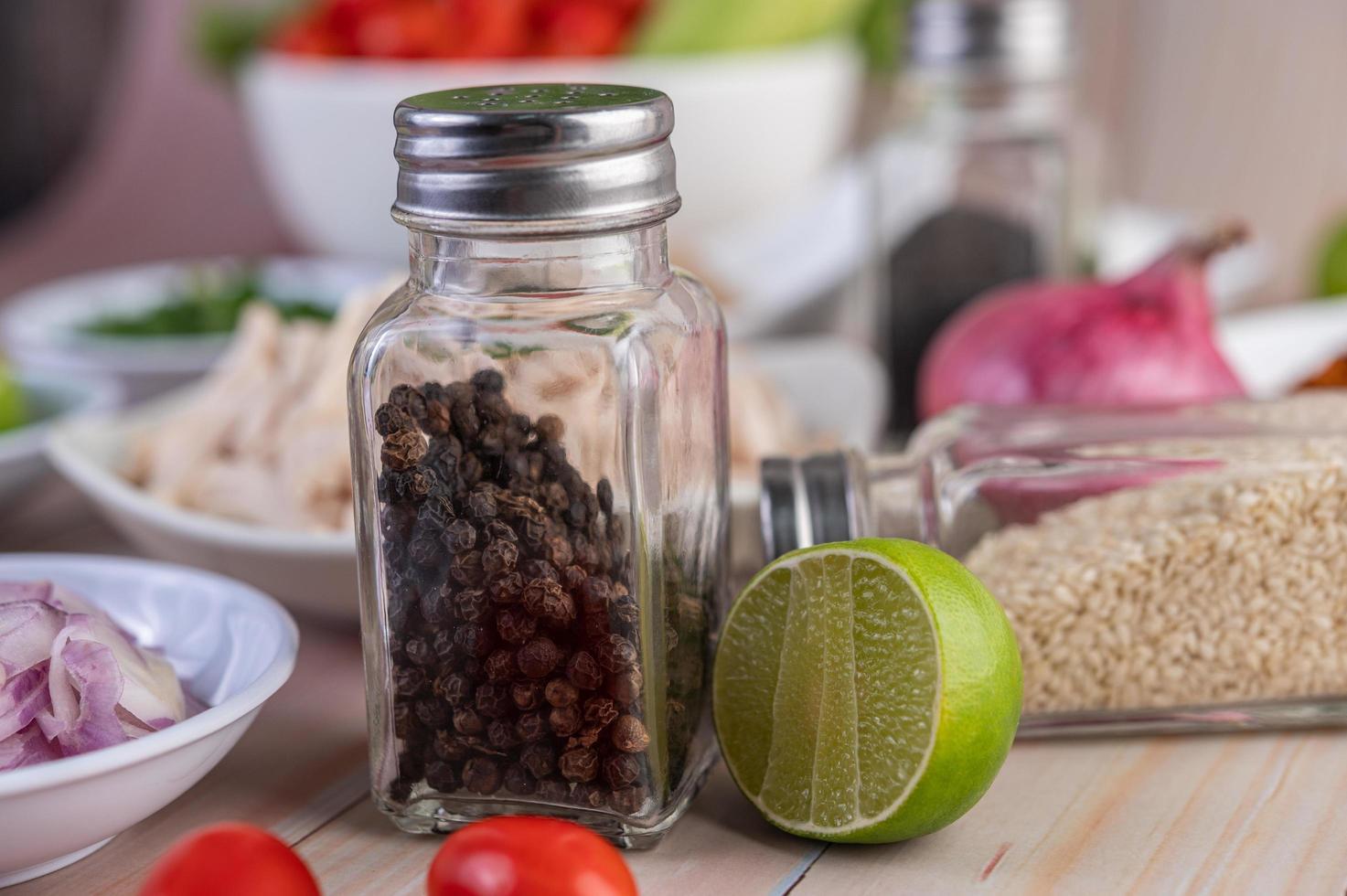 Pfefferstreuer auf Holztisch mit frischem Gemüse foto