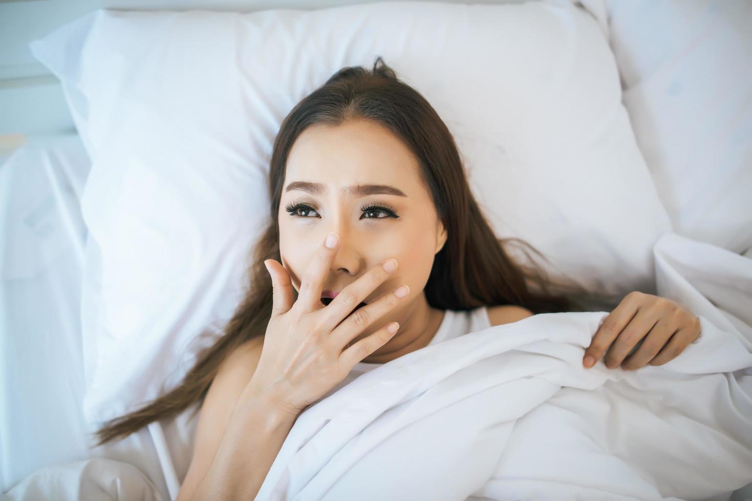 Frau wacht in ihrem Bett auf, faul am Morgen foto
