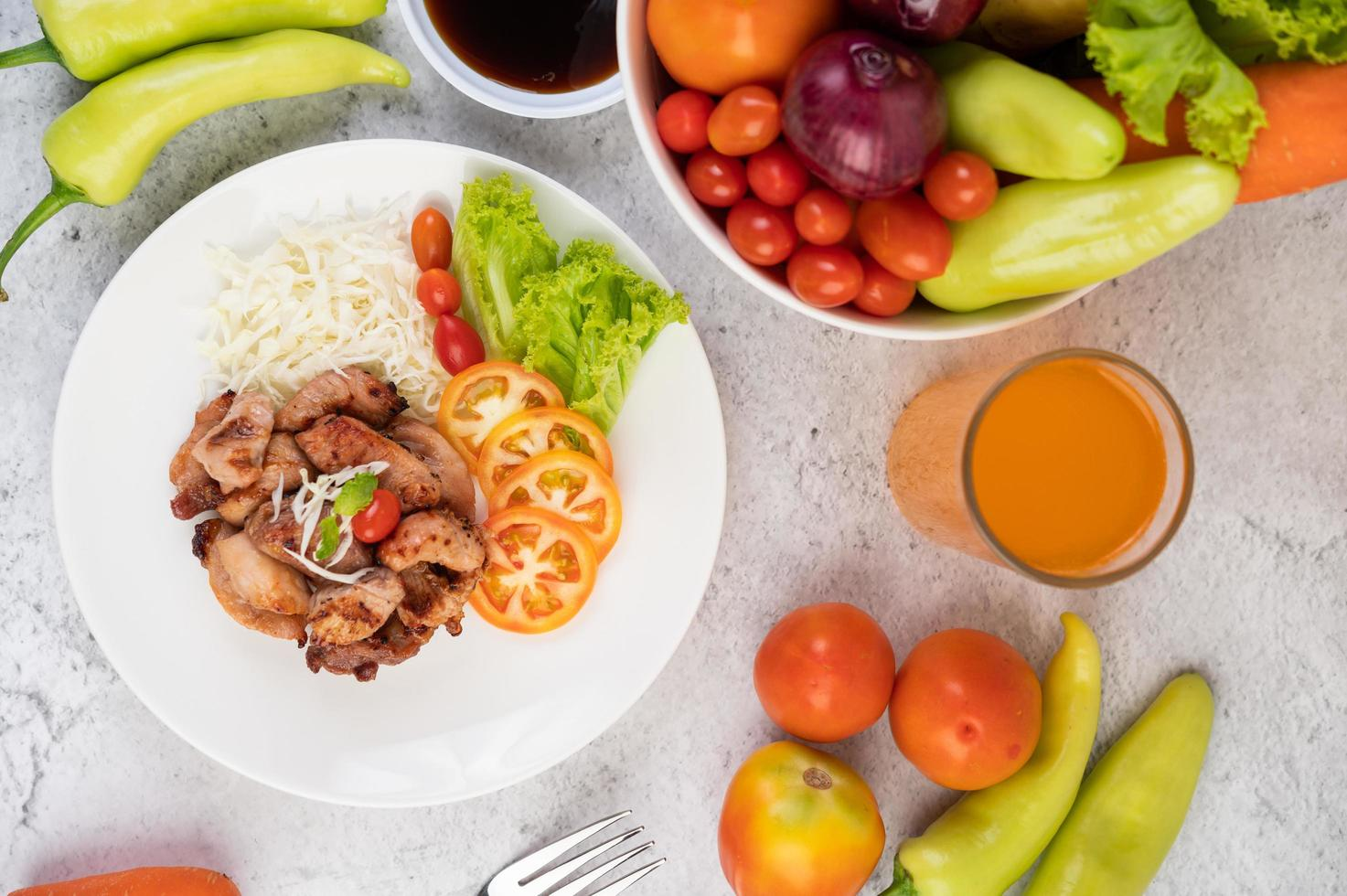 Gegrilltes Schweineschnitzel mit Tomaten und Salat foto