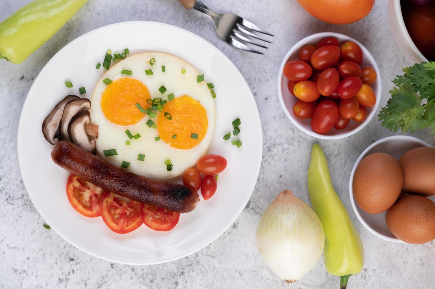 Frühstücksteller mit Spiegeleiern, Tomaten, chinesischer Wurst und Pilzen foto
