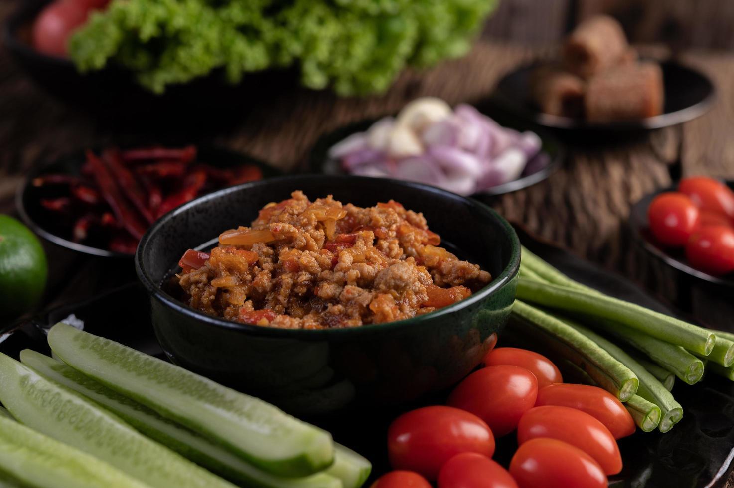 süßes Schweinefleisch mit Gurken, langen Bohnen, Tomaten und Beilagen foto