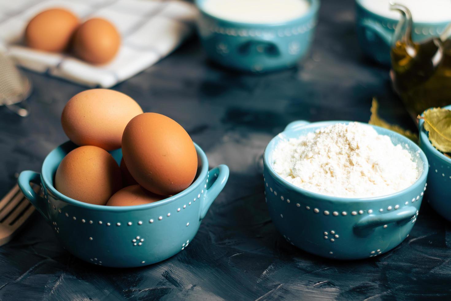 Eier und Mehl in Schalen foto