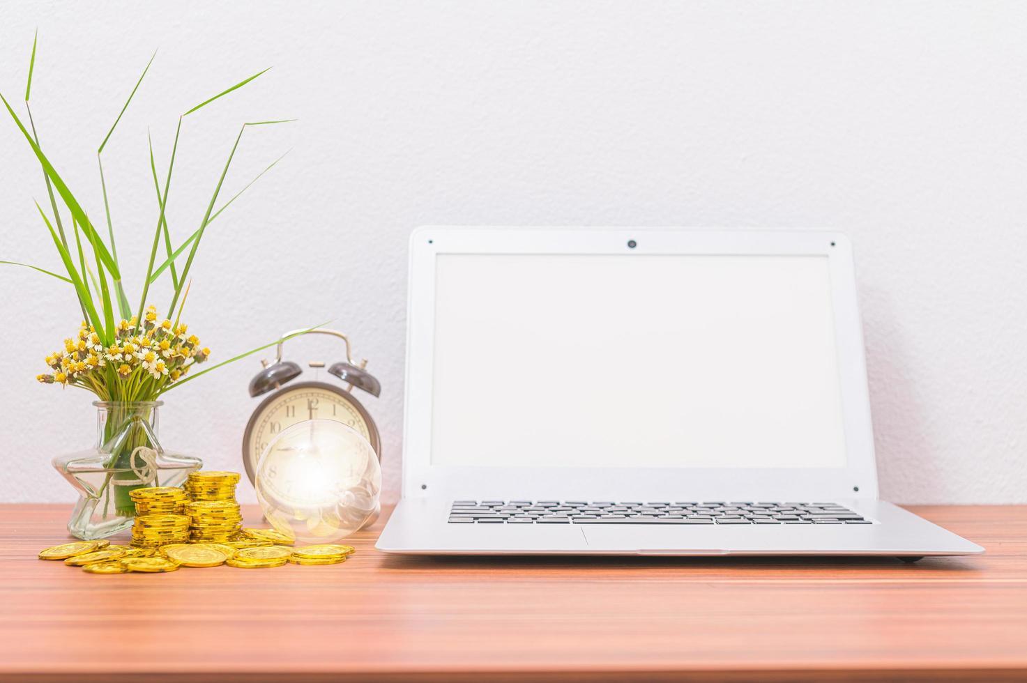 Laptop und Münzen auf dem Schreibtisch foto