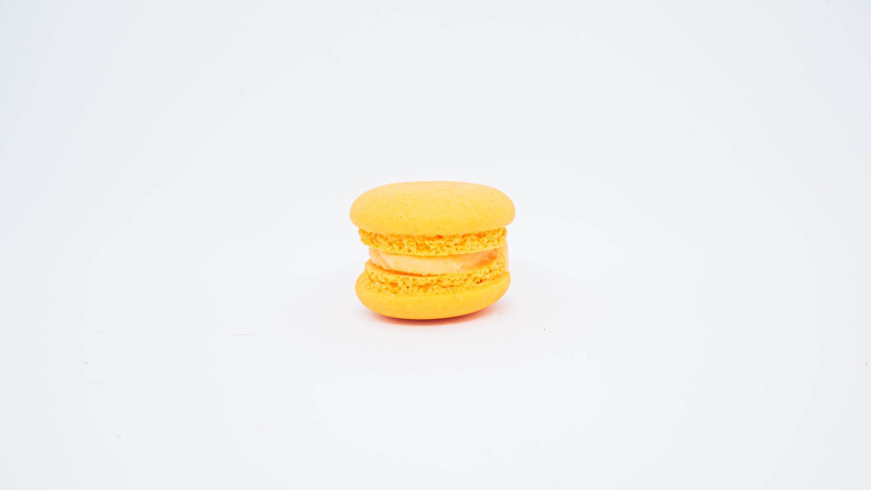gelber Macaron mit Cremeisolat auf weißem Hintergrund foto