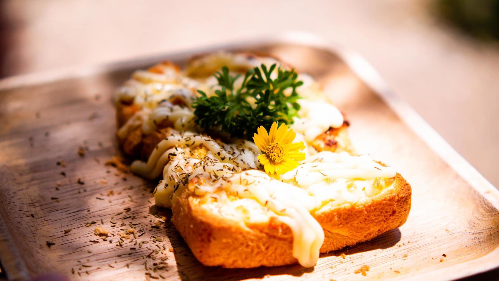 Scheibe geröstetes Weißbrot mit Mayonnaise bestrichen mit Blume und foto