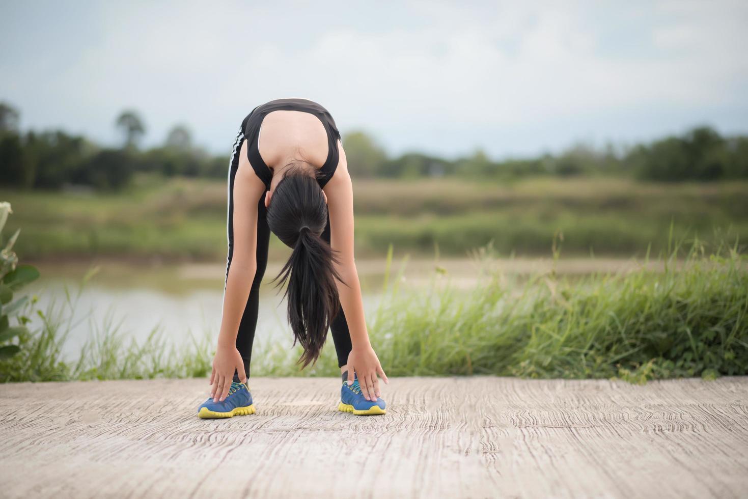 gesunde junge Frau, die sich im Freien für das Training aufwärmt foto