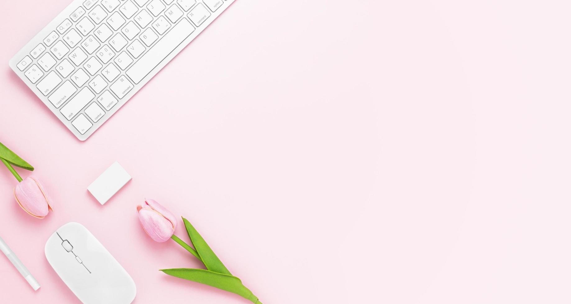 Minimaler Schreibtisch-Tisch mit Tastaturcomputer, Maus, weißem Stift, Tulpenblumen, Radiergummi auf einem rosa Pastelltisch mit Kopierraum für die Eingabe Ihres Textes, rosa Farbe Arbeitsplatzzusammensetzung, flache Lage, Draufsicht foto
