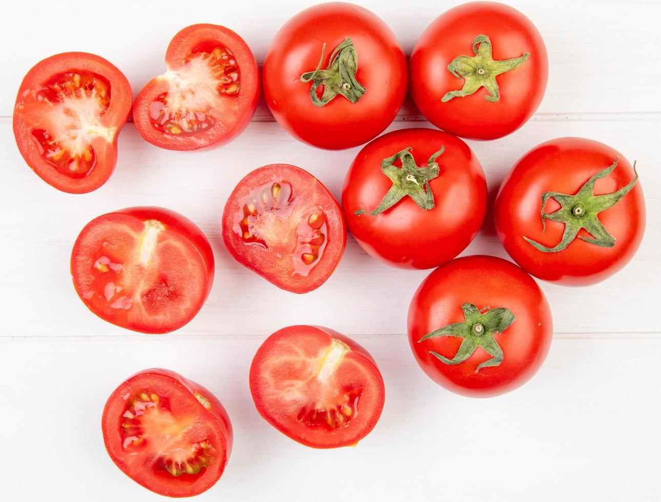 Draufsicht von geschnittenen und ganzen Tomaten auf hölzernem Hintergrund foto