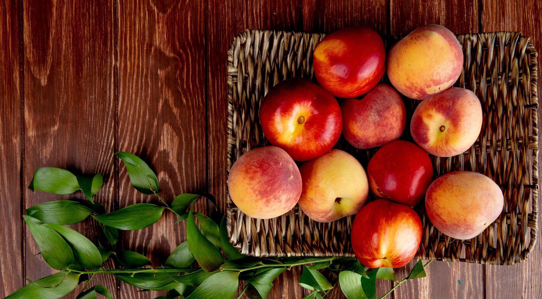 Draufsicht von Pfirsichen in Korbteller auf hölzernem Hintergrund verziert mit Blättern foto