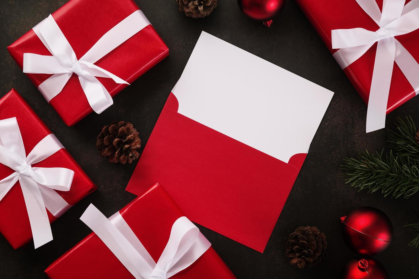leere weiße Grußkarte und Umschlagmodell mit Weihnachtsgeschenkdekorationen auf Schmutzhintergrund foto
