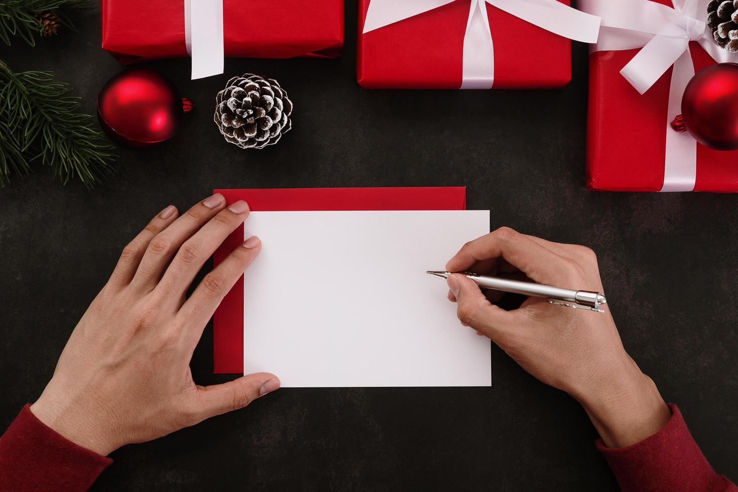 Hände, die weißes Grußkartenmodell mit Weihnachtsdekoration auf Schmutzhintergrund schreiben foto