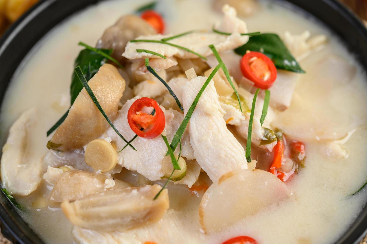 Tom Kha Kai Suppe mit Kaffirlimettenblättern, Zitronengras, roten Zwiebeln, Galangal und Chili foto