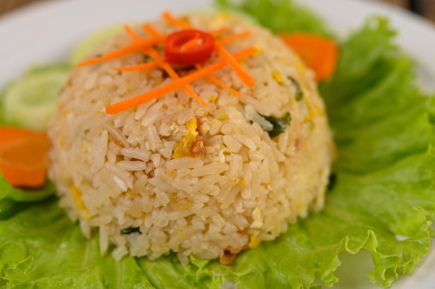 gebratener Reis auf einem weißen Teller mit Salat und Beilage foto