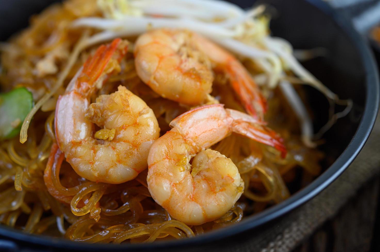 Pad Thai Shrimps in einer schwarzen Pfanne mit Eiern und Gewürzen foto
