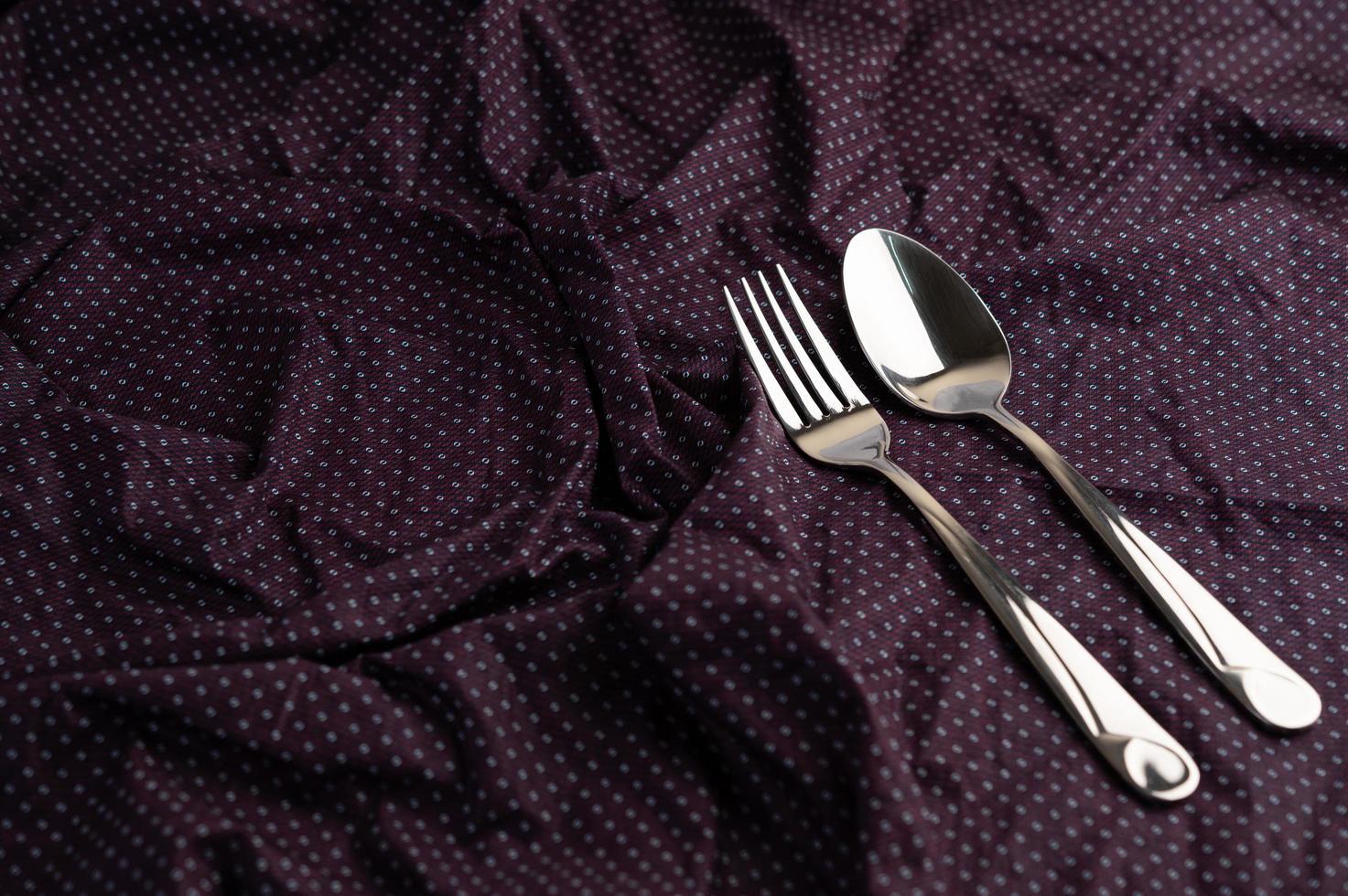 Löffel und Gabel auf ein zerknittertes Tuch gelegt foto