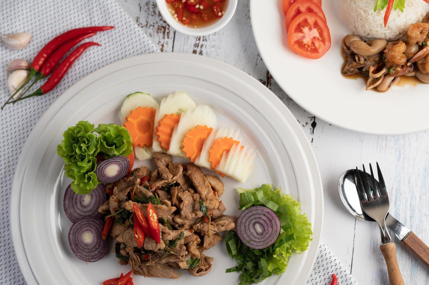Gebratenes Schweinefleischbasilikum mit Karotten, Gurken und Zwiebeln foto